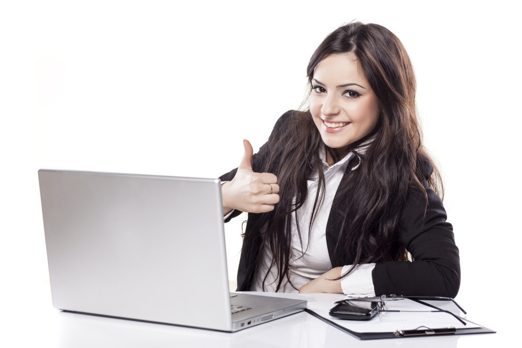 smiling business woman at desk with laptop showing thumbs up